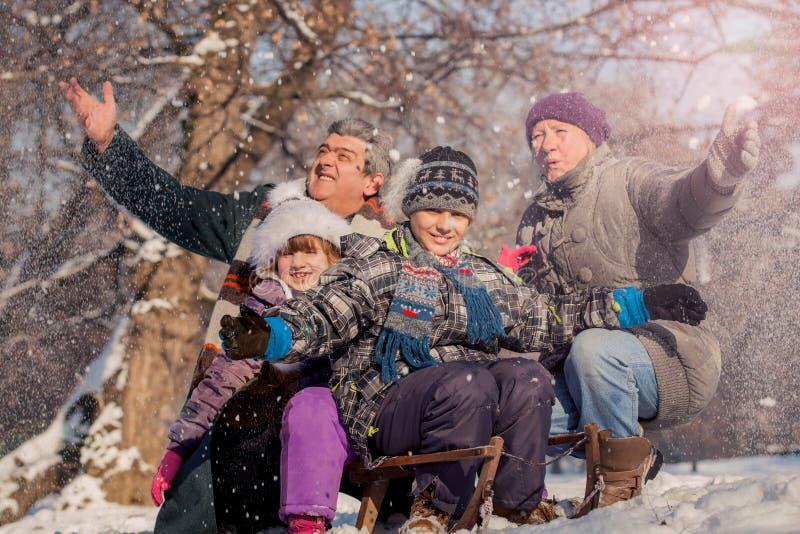 Morföräldrar med barnbarn som tycker om på snön, vinterfami royaltyfri fotografi