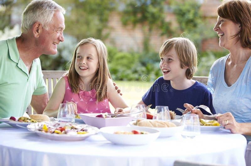 Morföräldrar med barnbarn som tycker om utomhus- mål arkivbilder