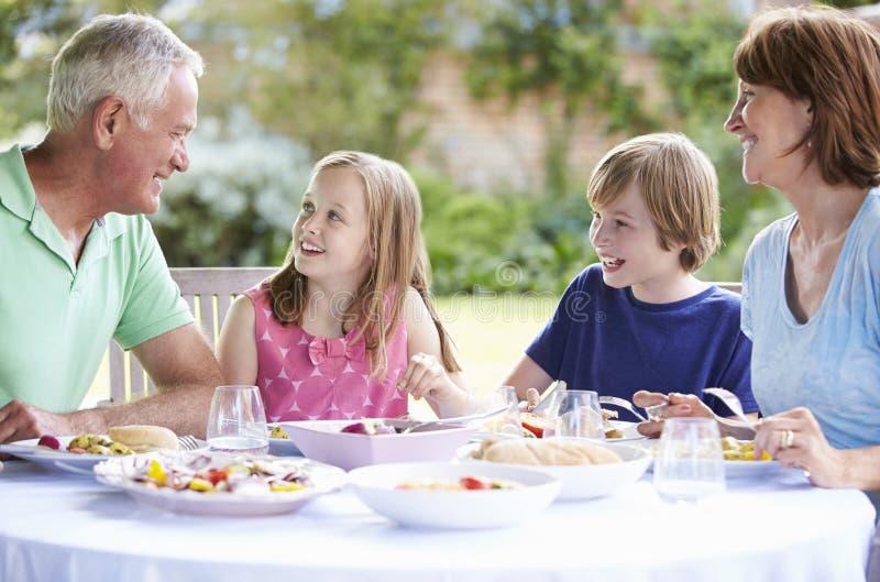 Morföräldrar med barnbarn som tycker om utomhus- mål royaltyfri bild