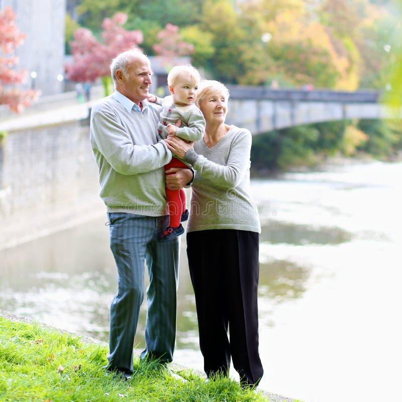 Morföräldrar med sondottern som går i parkera arkivfoton