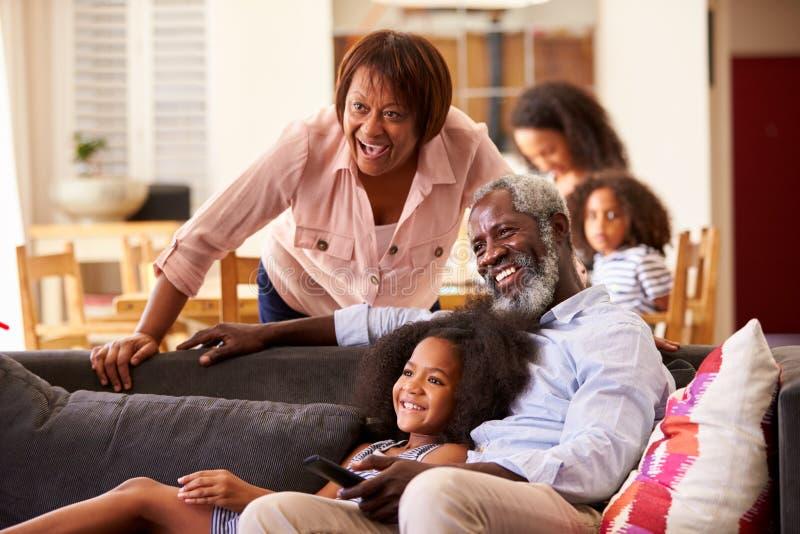 Morföräldrar med sondottern som sitter på Sofa At Home Watching Movie med familjen i bakgrund royaltyfri fotografi