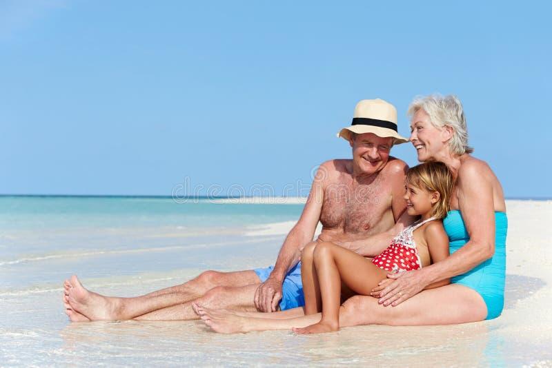 Morföräldrar med sondottern som tycker om strandferie arkivbild