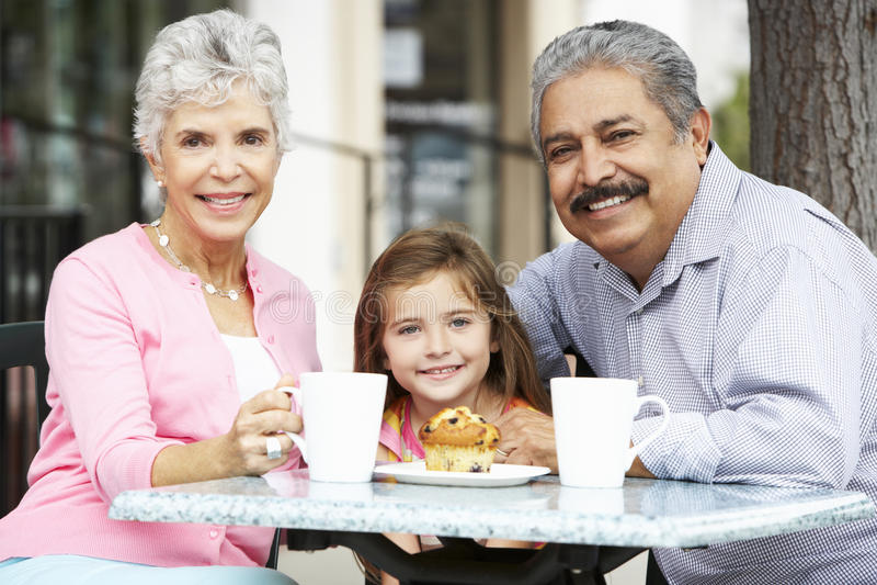 Morföräldrar med sondottern som tycker om mellanmålet på utomhus- CafÅ ½ arkivbild
