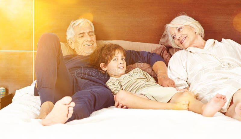 Morföräldrar med sonsonen på säng royaltyfri bild