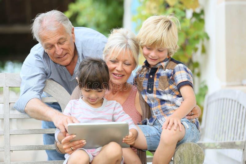Morföräldrar och barnbarn som använder minnestavlan royaltyfria foton