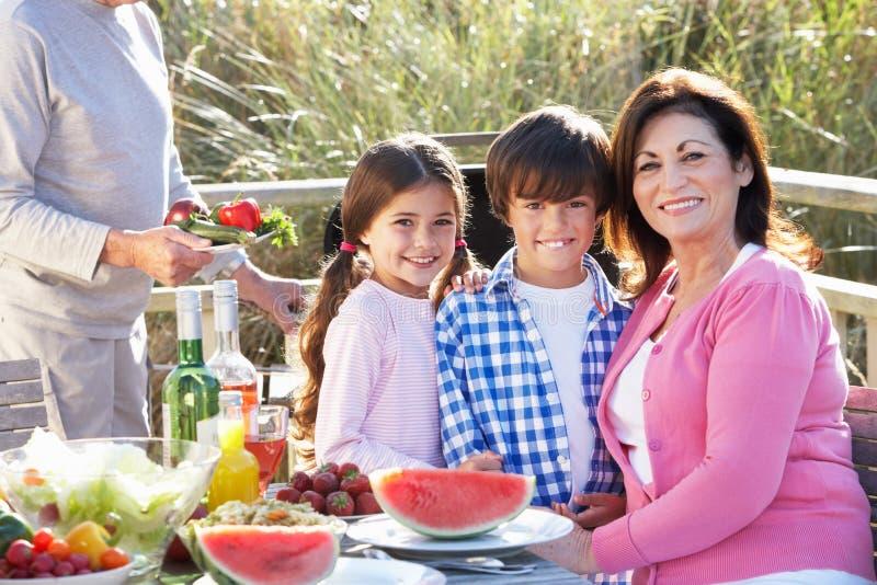 Morföräldrar och barnbarn som har den utomhus- grillfesten arkivbild