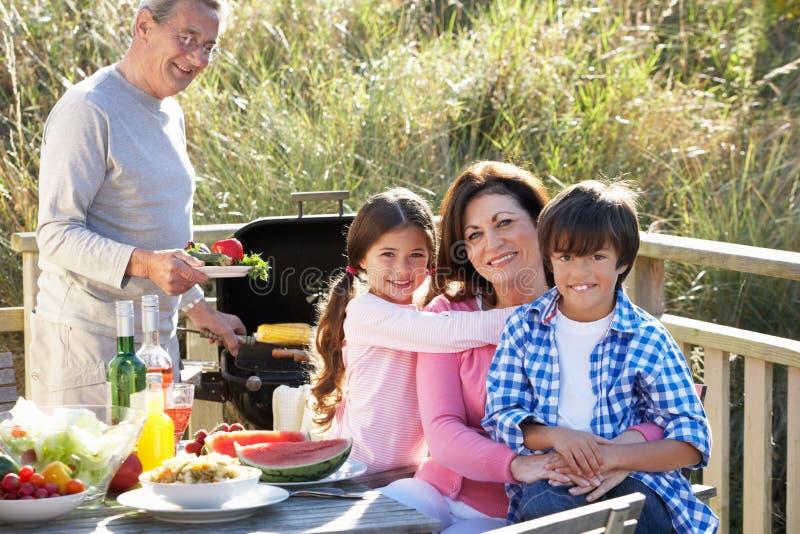 Morföräldrar och barnbarn som har den utomhus- grillfesten royaltyfria bilder