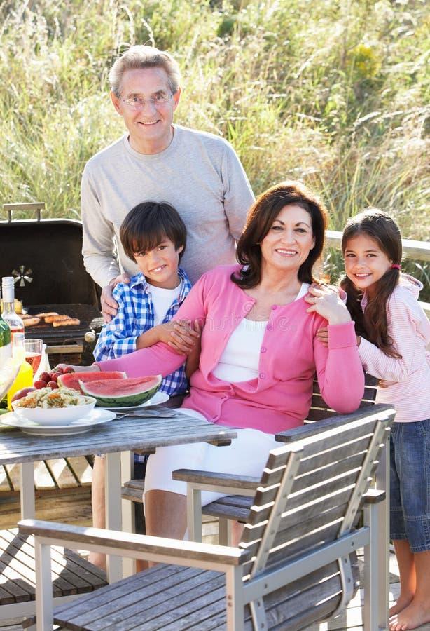 Morföräldrar och barnbarn som har den utomhus- grillfesten fotografering för bildbyråer