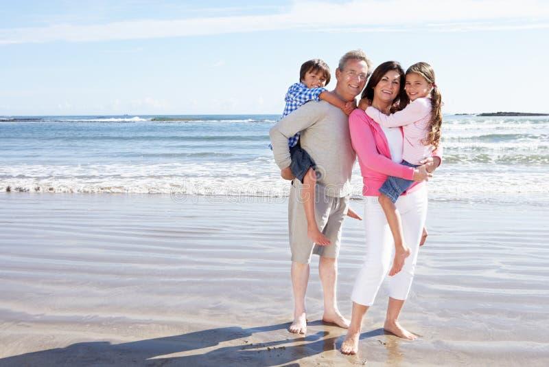 Morföräldrar och barnbarn som har gyckel på strandferie arkivfoto