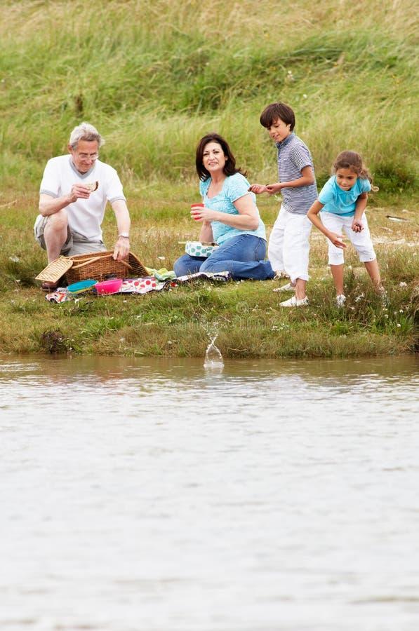 Morföräldrar och barnbarn som har picknicken på flodstrand royaltyfri fotografi