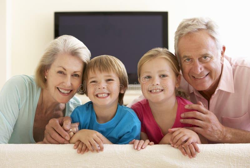 Morföräldrar och barnbarn som hemma håller ögonen på Widescreen TV arkivfoto