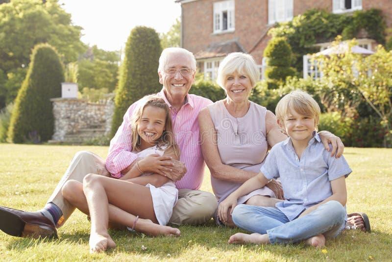 Morföräldrar och barnbarn som sitter på gräs i en trädgård arkivbild
