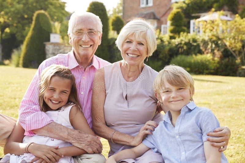 Morföräldrar och barnbarn som sitter på gräs i en trädgård royaltyfri fotografi