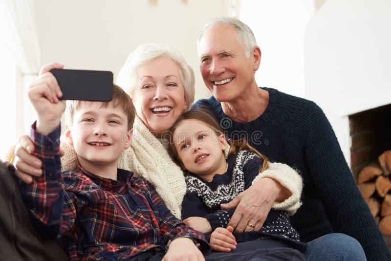 Morföräldrar och barnbarn som sitter på Sofa Taking Selfie arkivbilder