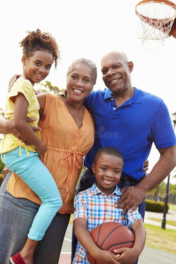 Morföräldrar och barnbarn som spelar basket tillsammans royaltyfria bilder