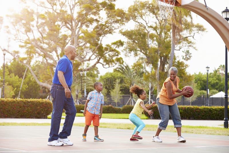 Morföräldrar och barnbarn som spelar basket tillsammans arkivfoton