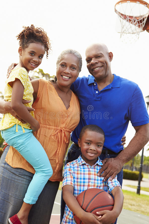 Morföräldrar och barnbarn som spelar basket tillsammans arkivfoto