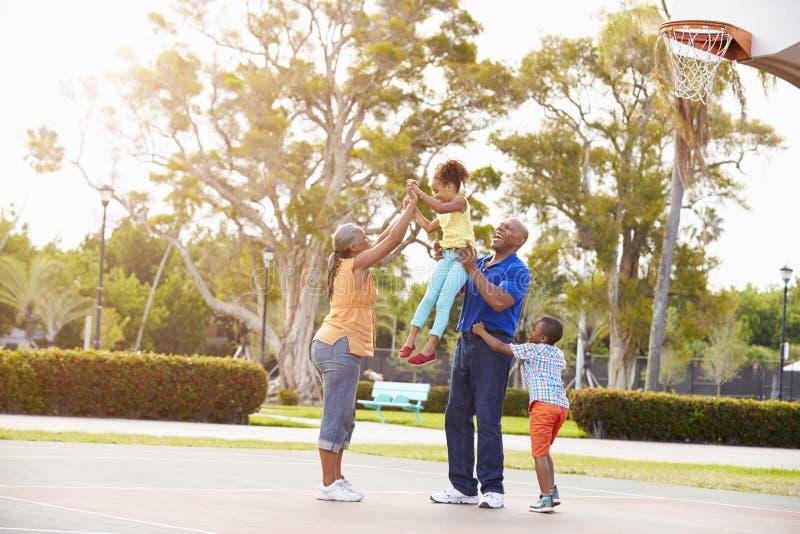 Morföräldrar och barnbarn som spelar basket tillsammans arkivbilder