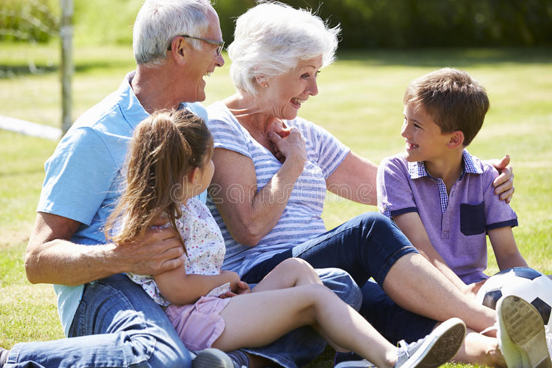 Morföräldrar och barnbarn som spelar fotboll i trädgård arkivfoto
