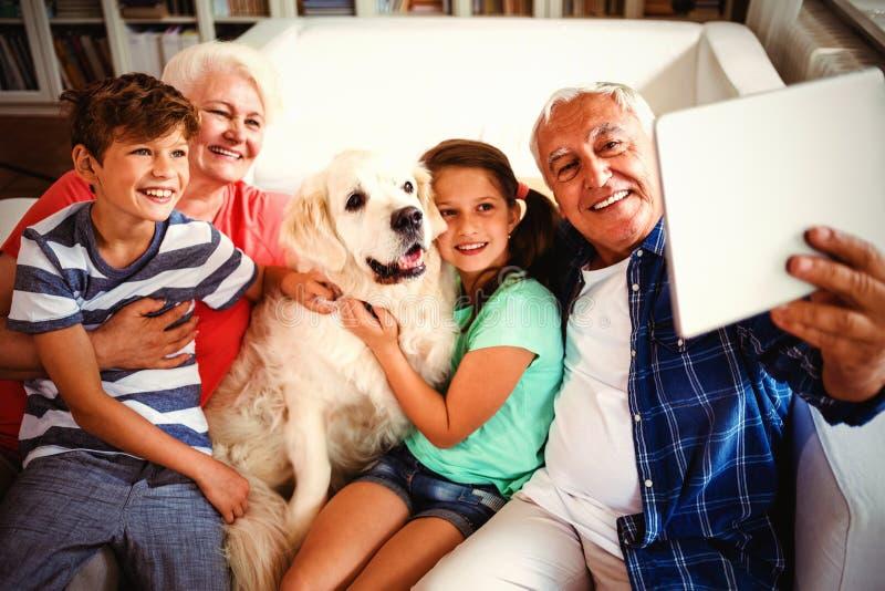 Morföräldrar och barnbarn som tar en selfie med den digitala minnestavlan royaltyfri foto