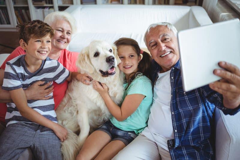 Morföräldrar och barnbarn som tar en selfie med den digitala minnestavlan arkivbild