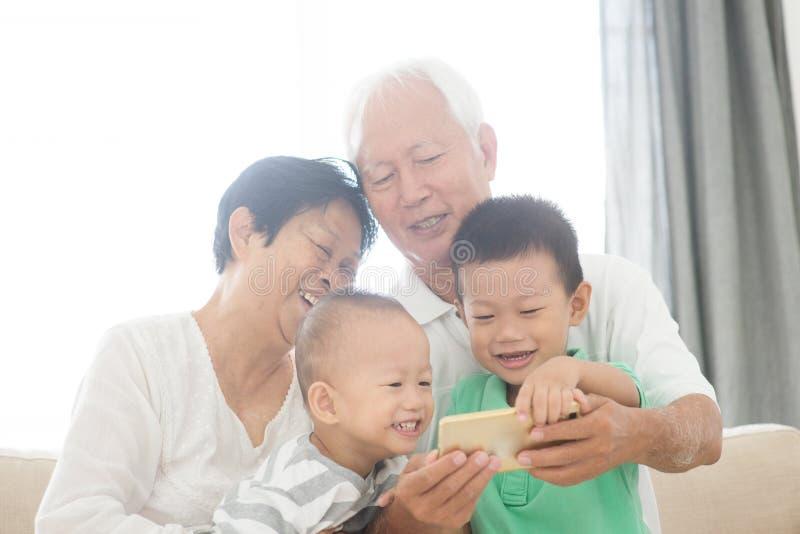 Morföräldrar och barnbarn som tar selfie genom att använda smarta telefoner royaltyfri fotografi