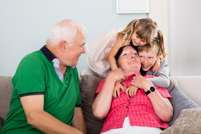 Morföräldrar och barnbarn som tillsammans spelar royaltyfri fotografi