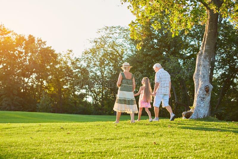 Morföräldrar och barnbarn som utomhus går royaltyfri foto