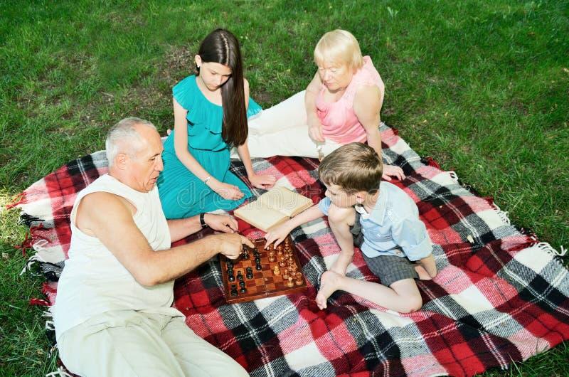 Morföräldrar och barnbarn vilar i parkera Top beskådar royaltyfria bilder