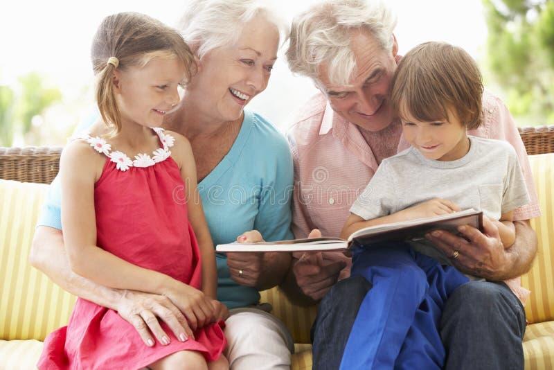 Morföräldrar och barnbarnläsebok på trädgårds- Seat arkivfoton