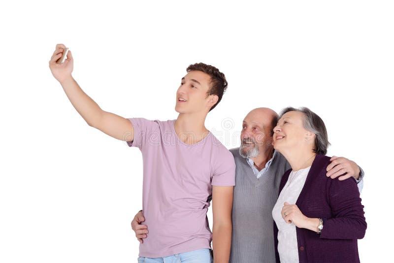 Morföräldrar och deras sonson som tar en selfie fotografering för bildbyråer