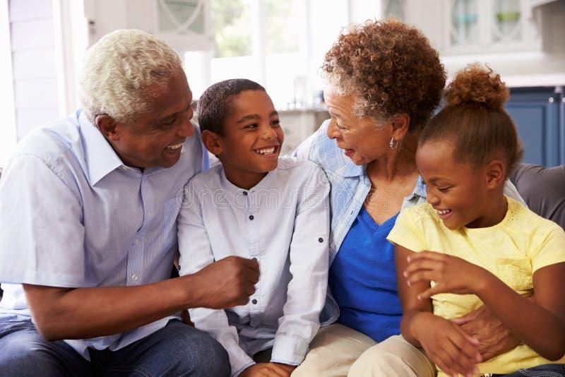 Morföräldrar och deras unga barnbarn som hemma kopplar av royaltyfri bild