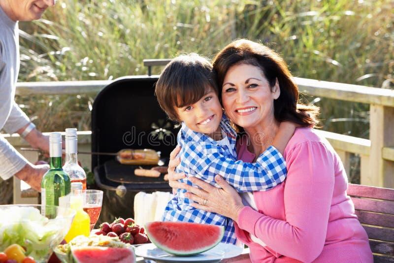 Morföräldrar och sonson som har den utomhus- grillfesten fotografering för bildbyråer