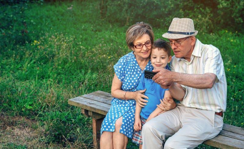 Morföräldrar och sonson som tar selfie som sitter på en bänk arkivbild