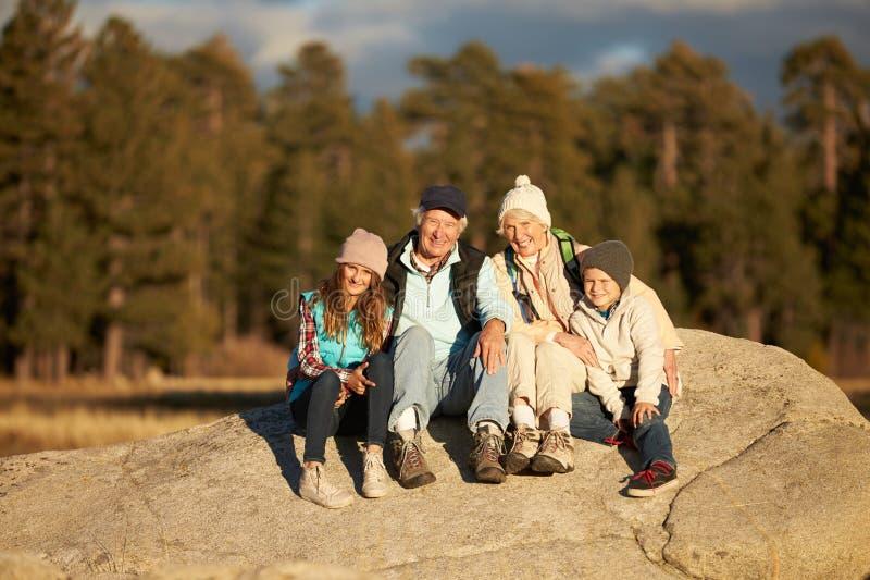 Morföräldrar och ungar som sitter på stenig utlöpare nära en skog royaltyfri fotografi