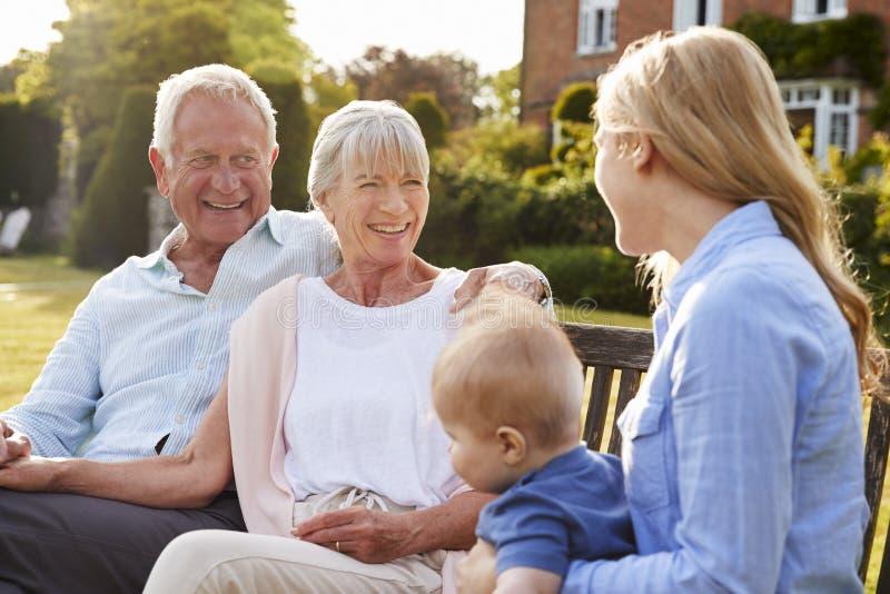 Morföräldrar Sit Outdoors With Baby Grandson och vuxen människadotter arkivbilder