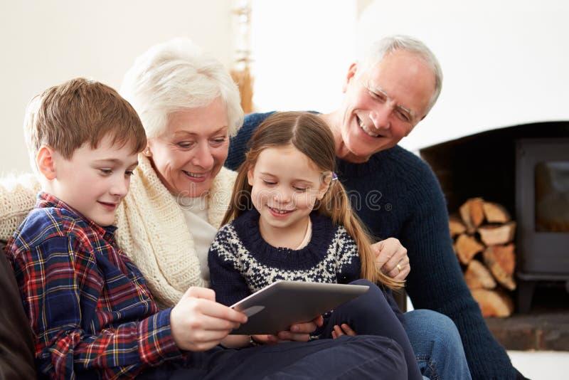 Morföräldrar som använder den Digital minnestavlan på Sofa With Grandchildren royaltyfri bild