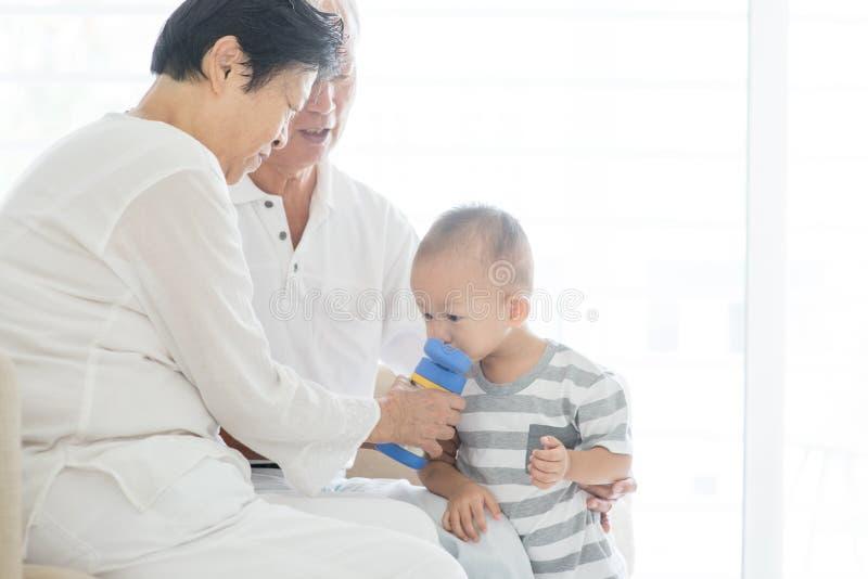 Morföräldrar som babysitting barnbarnet arkivbilder