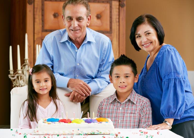 Morföräldrar som firar barns födelsedagtårtan royaltyfria foton