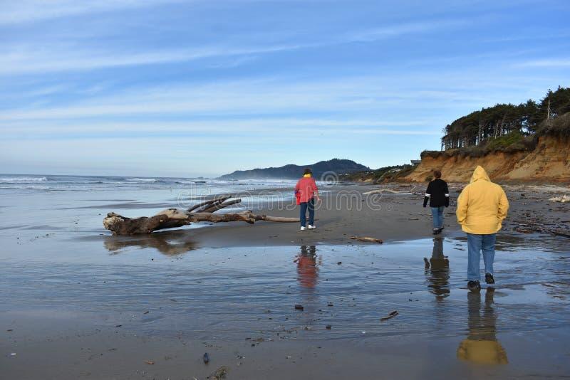 Morföräldrar som går stranden med ett barnbarn royaltyfri fotografi