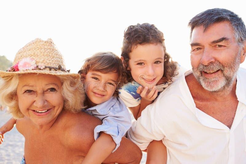 Morföräldrar som ger barnbarn ridturer på axlarna på sommarferie arkivbilder