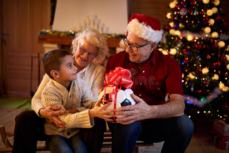Morföräldrar som ger gåvasonsonen på julhelgdagsaftonen royaltyfri bild