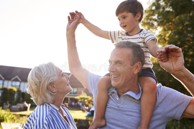 Morföräldrar som ger sonsonritt på skuldror i sommar, parkerar mot att blossa solen royaltyfri bild