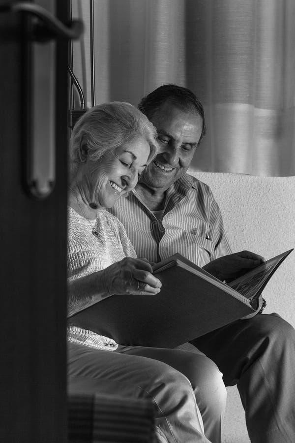 Morföräldrar som granskar deras album av familjfotografier royaltyfri bild