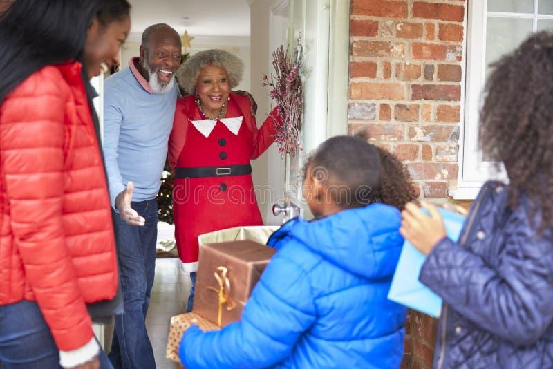 Morföräldrar som hälsar modern och barn, som de ankommer för besök på juldagen med gåvor royaltyfria foton