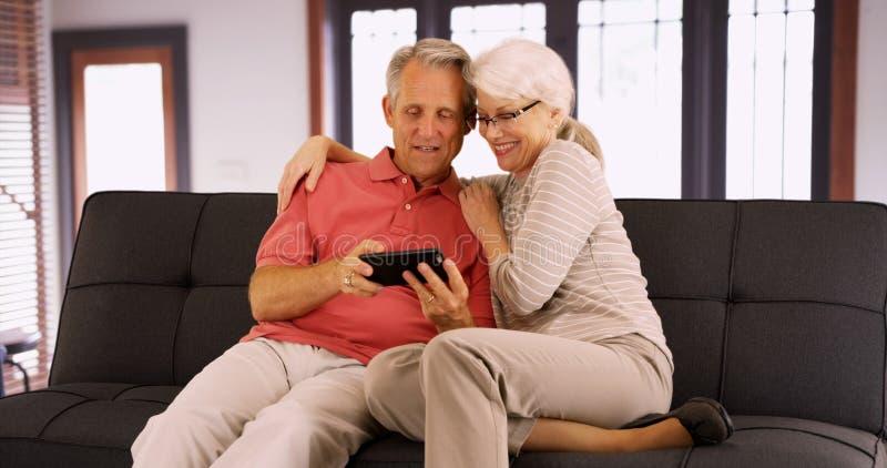 Morföräldrar som hemma tar selfies arkivbild