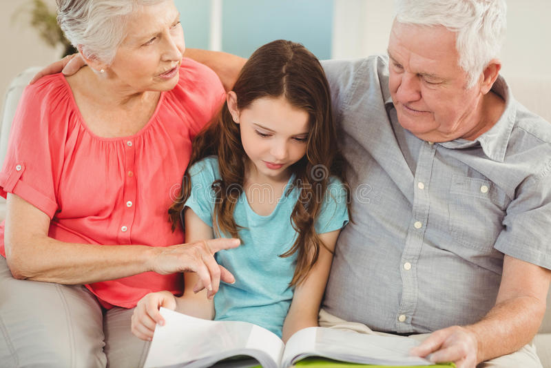Morföräldrar som läser en bok med sondottern royaltyfri bild