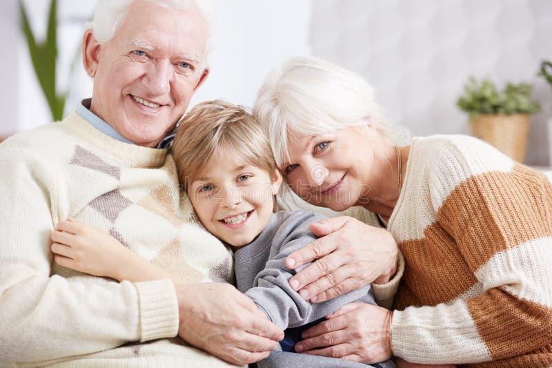Morföräldrar som omfamnar deras sonson arkivfoton