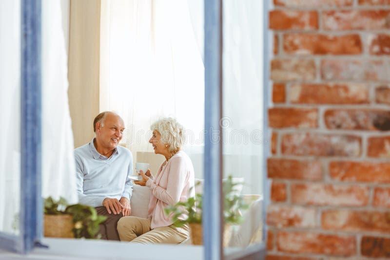 Morföräldrar som sitter på soffan arkivbilder