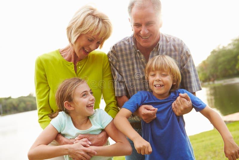 Morföräldrar som spelar med barnbarn utomhus royaltyfri fotografi
